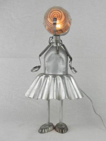 Personnage féminin avec gourde et moule à gâteau en aluminium. Assemblage lumineux d'un bol, deux mini moules et une pince à escargot. Lampe figurative