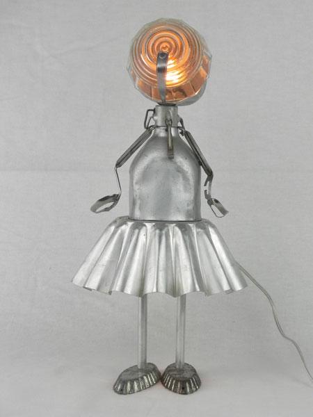 Gourdol. Personnage féminin avec gourde et moule à gâteau en aluminium. Assemblage lumineux d'un bol, deux mini moules et une pince à escargot. Lampe figurative