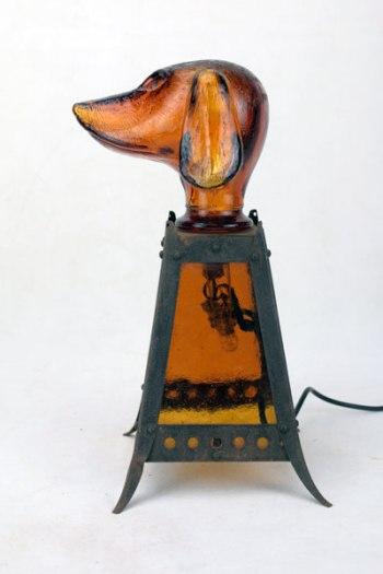 Sculpture chien royal lumineux. Assemblage d'un bouchon de carafe en forme de chien, lanterne ancienne avec des verres cathédrale marron.