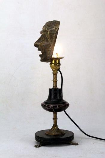 Sculpture assemblage d'antiquités. Masque miniature décoratif et bougeoir.