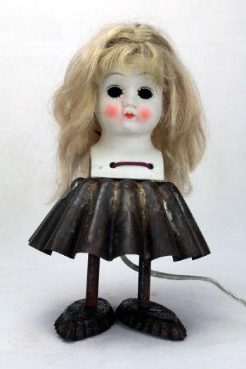 Sculpture poupée porcelaine gâteau. Composition: tête de poupée en porcelaine, moule à brioche, 2 petits moules en forme de barquette, lacet.