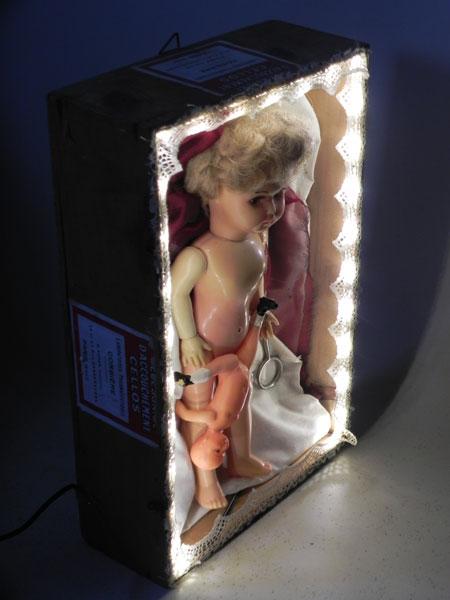 """Boite """"nécessaire d'accouchement Cellos"""" mise scène avec de la ouate, des dentelles, ciseaux, pinces, poupées anciennes."""