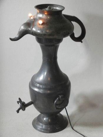 Personnage lumineux avec objets en étain. Assemblage d'une théière et d'un pot avec robinet.