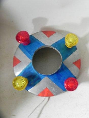 Macaron lumineux aluminium fête foraine. Composé d'un cône peint en rouge et bleu et quatre ampoules de fête foraine rouges et jaunes.