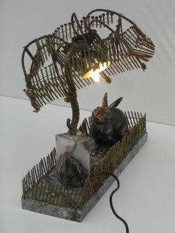 Composition lumineuse avec objets bizarres. Assemblage d'un lapin en fonte sur une plaque de marbre, un élément d'applique, recharge clous pour pistolet à clous.