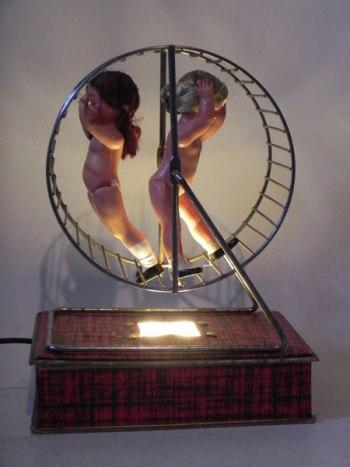 Poupées dans une roue de hamster sur une jolie boite qui les éclaire. Association d'objets, association d'idées.