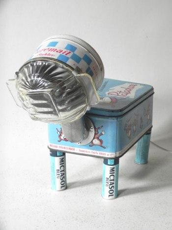 """Animal lumineux à quatre pattes avec boites anciennes. Composition: boite à chaussure """"patachou"""", boite """"curemail"""", 4 tubes de médicament, bol en verre."""