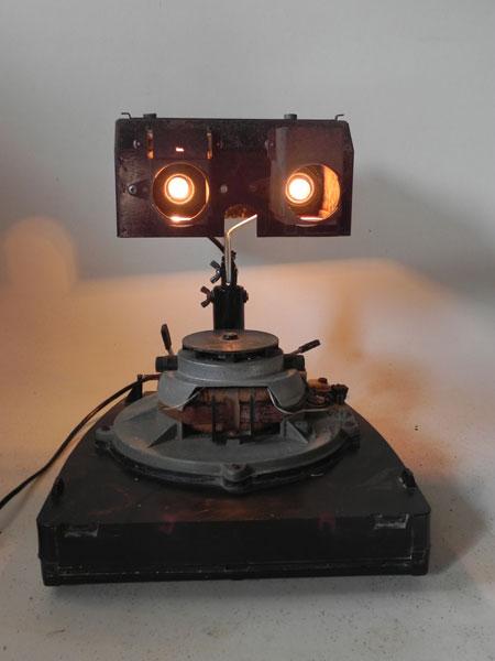 """Sculpture véhicule lumineux assemblage d'un intérieur de cireuse à roulettes, un capot de protection """"plot central de protection"""" et deux lentilles de projection."""