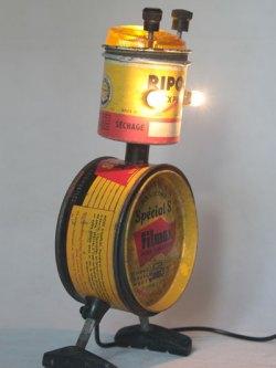 """Robot insecte avec des boites vintages. Assemblage """"Ripolin express, séchage rapide"""" et """"Filmex pour carrosserie, super polish en pâte aux silicones"""", avec cabochon lumineux et freins de vélo."""