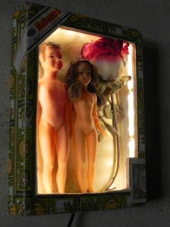 """Roméo et Juliette nus dans une boite à cigares """"Romeo y Julieta"""" en bois, fleur en tissus et 2 poupées en plastique. Boite lumineuse."""