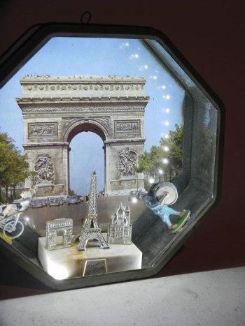 Composition dans une boite à gâteaux la Caennaise. boite en métal imprimée Arc de triomphe, personnage en plomb, fanfare, cycliste et monuments parisiens en plastique.