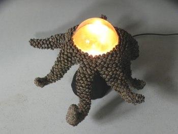 Sculpture lumineuse avec tentacules de pommes de pin. Pommes de pin démontées, recomposées en tentacules autour d'un verre de cafetière.