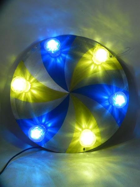 Applique soucoupe volante festive. Composition: cône peint en bleu et jaune, ampoules de fête foraine bleues et jaunes .