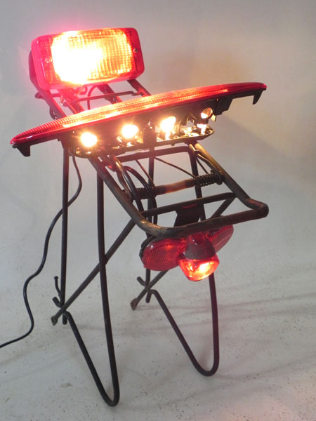 Assemblage lumineux morceaux d' auto moto vélo, feu arrière sur une structure porte bagage. Rouge et noir.