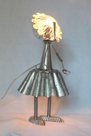 Détournement de moule motif cachemire, personnage féminin avec moules à gâteaux, cône, moule à barquettes, pince à escargot, petite cuillère, bol.