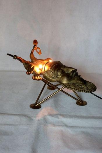 Scarabée lumineux avec masque africain. détournement d'un masque décoratif d'Afrique en fonte doré sur un porte bougies. Assemblage, animal.