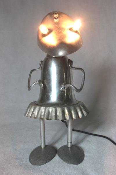 Lampe féminine par assemblage d'aluminium. Composition: embauchoir, coupe de sport, moule à tartelette, cuillères, anses .