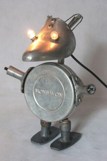 """Sculpture lumineuse en aluminium. Assemblage d'un embauchoir, une boite à savon """"Monsavon"""", deux poignées de fenêtre et de casserole et deux bigoudis ."""