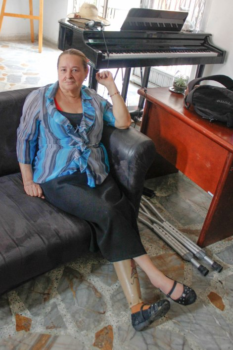 "Margoth Yepes, known as ""La Abuela Rapera,"" sits in the common room of ""La Casa Morada."""