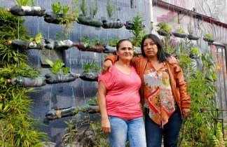 """Women Walking for Truth members Blanca Nidia Perez Botero (right) and Luz Elena Galeano Laverde (left) outside of """"La Casa Morada,"""" an activist meeting space in the Comuna 13 neighborhood of Medellín."""