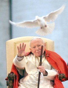 """Pope John Paul II looks at a white dove released in honor of his repeated calls for peace by Roman youths in St. Peter's Square at the Vatican, Thursday, April 10, 2003, during a special meeting organized in preparation of the next 18th World Youth Day that will be held in 2005 in Cologne, Germany. The pontiff urged youths to become """"promoters of the culture of peace"""" in a world torn by terrorism and war. (AP Photo/Massimo Sambucetti)"""