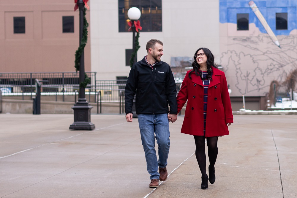 Engaged couple walking holding hands outside of the Union Depot in Saint Paul, MN.
