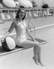 950s smiling bathing beauty in satin one piece swim suit sitting on diving board holding beach ball da/from www.corbis.com