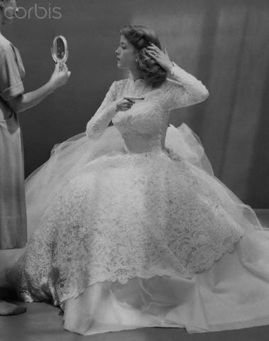 Bride in wedding gown combing her hair, 1950. da/from www.corbis.com