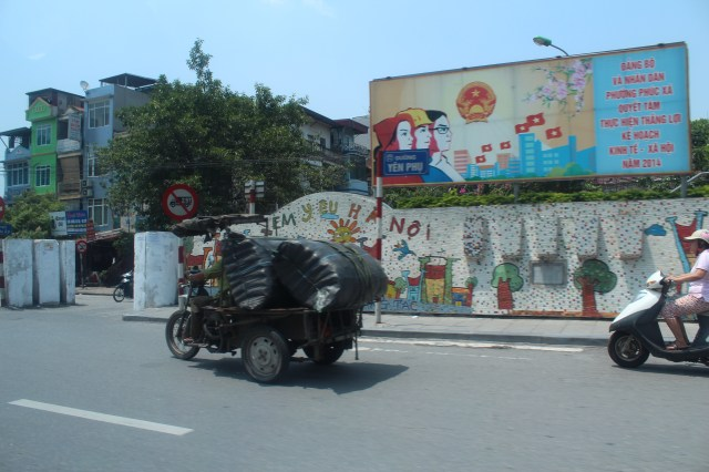 Heavily laden motorbikes in front of Hanoi's mural wall