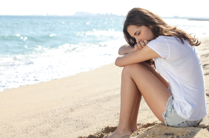 Portrait of a worried girl sitting on the beach