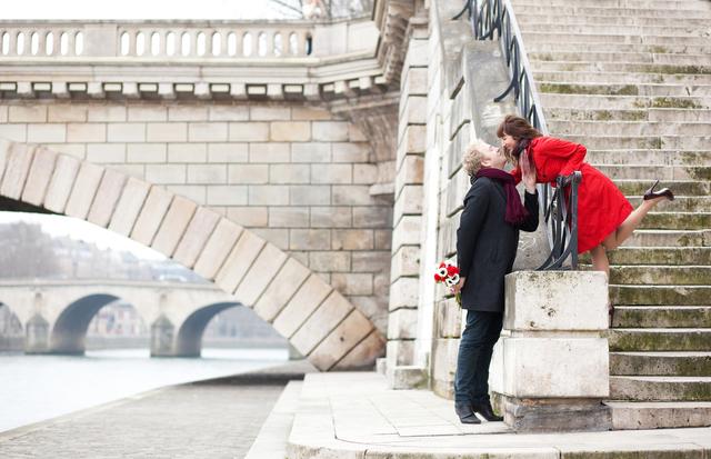 Beautiful romantic couple kissing on a Parisian embankment at sp