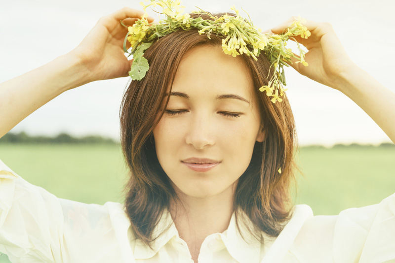 Beautiful woman with wreath of yellow wildflowers