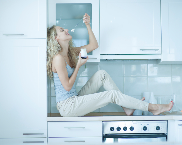 Side view of young woman eating yogurt while sitting on kitchen counter
