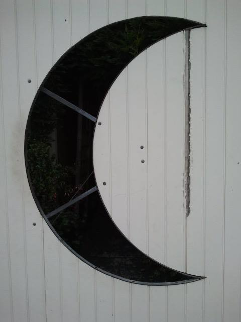 A peek into a courtyard through a half-moon cutout in the fence