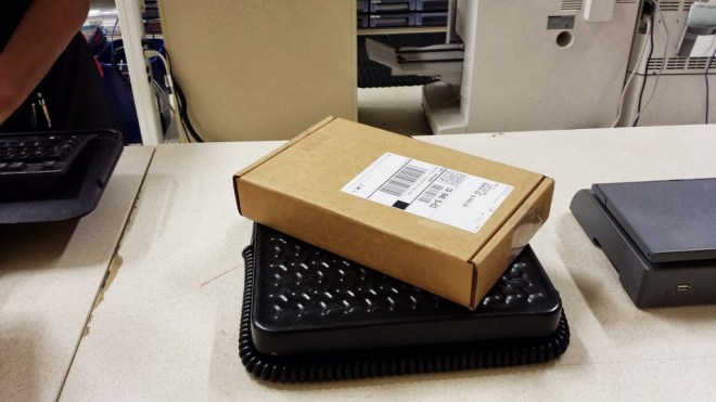 UPS mailing carton containing Google Glass sitting atop the scale at UPS
