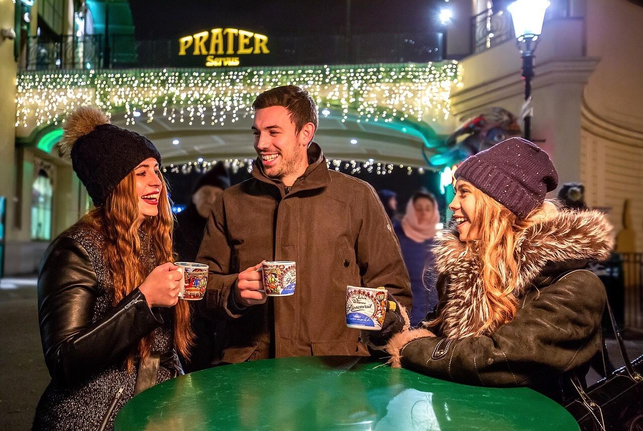 Friends drinking Gluehwein, drinking mulled red wine, Christmas market
