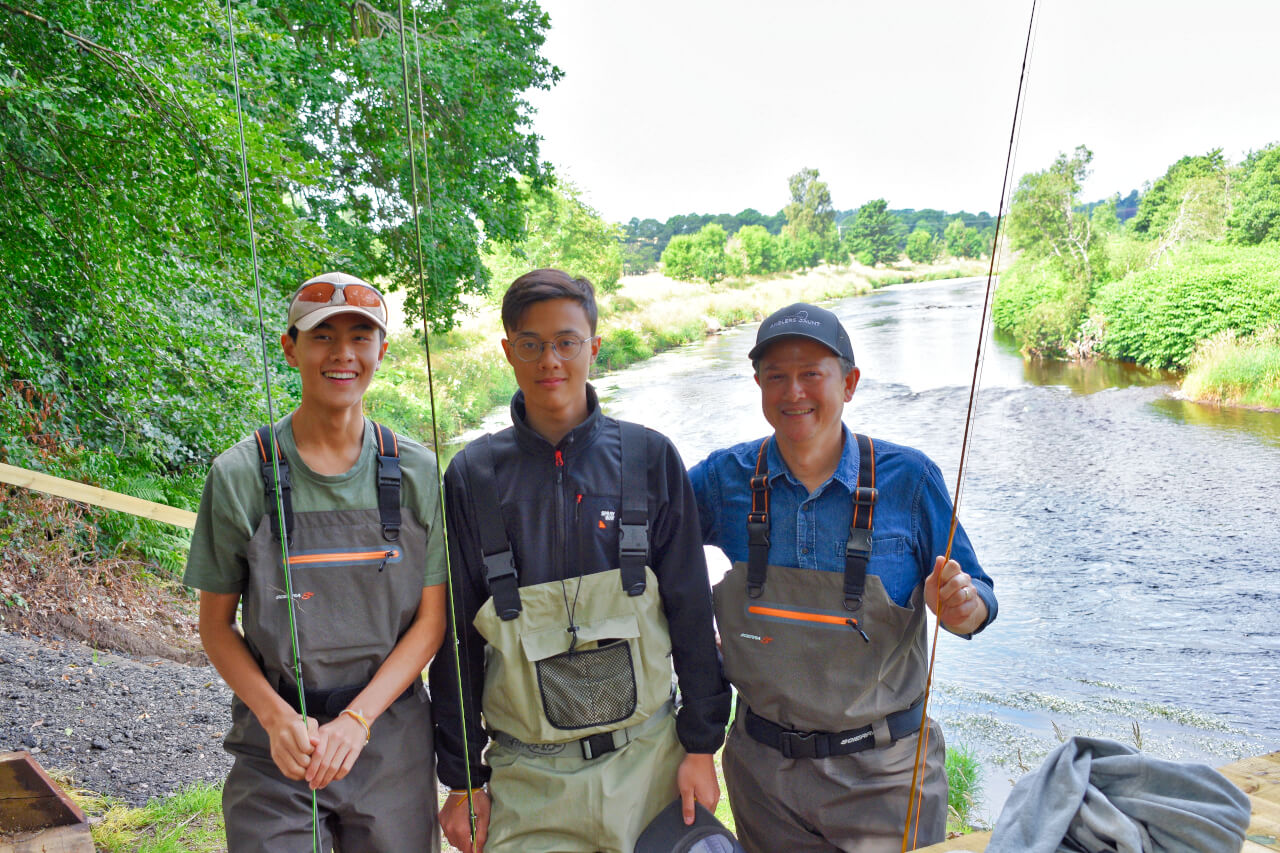 family standing together beside scottish river on their family fishing trip