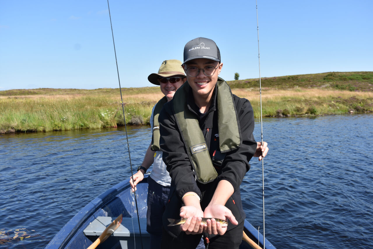young lad holding his first brown trout caught fly fishing on loch during family fishing trip in scotland