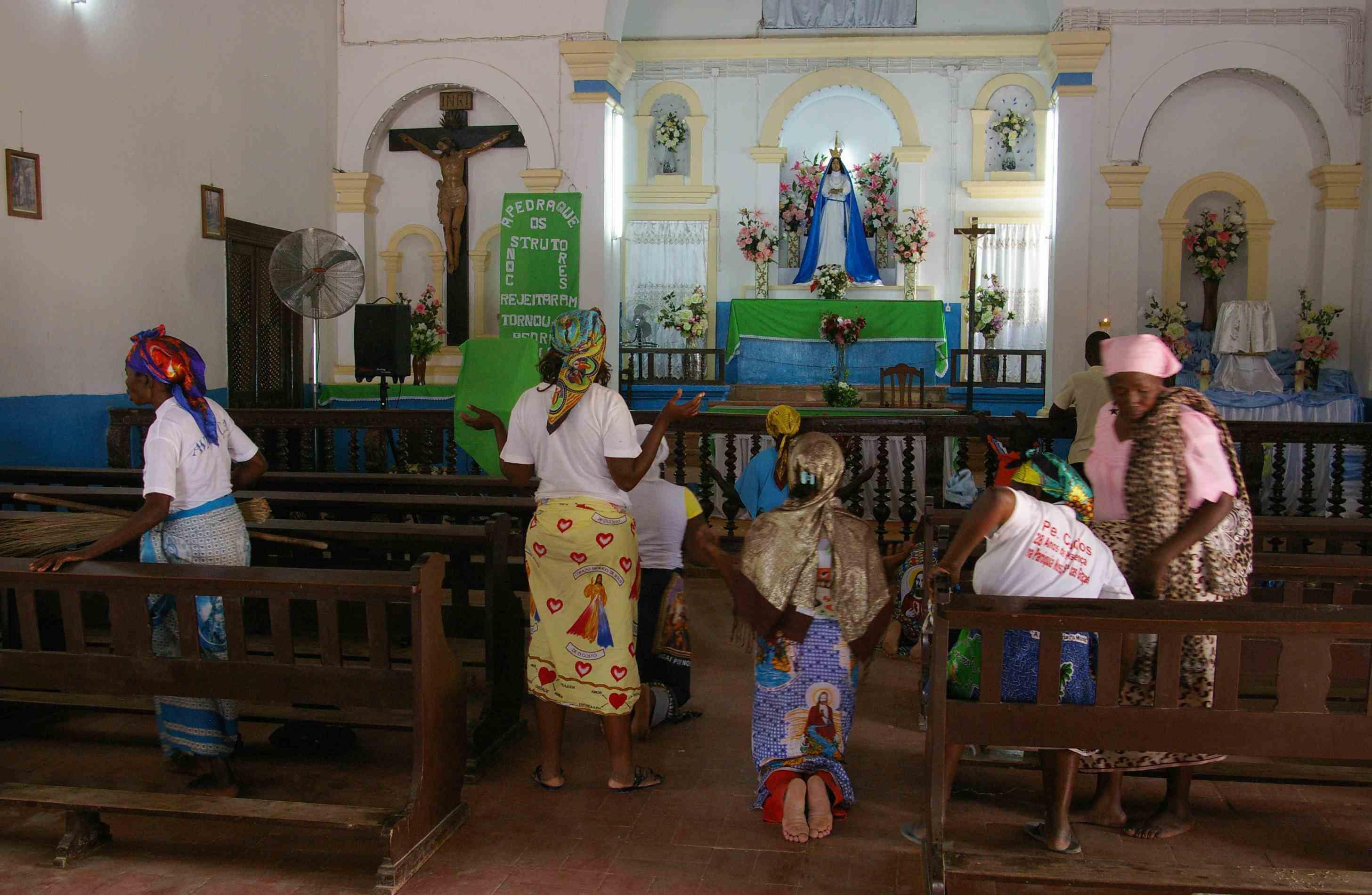Devotees praying to Mama Muxima inside the church.