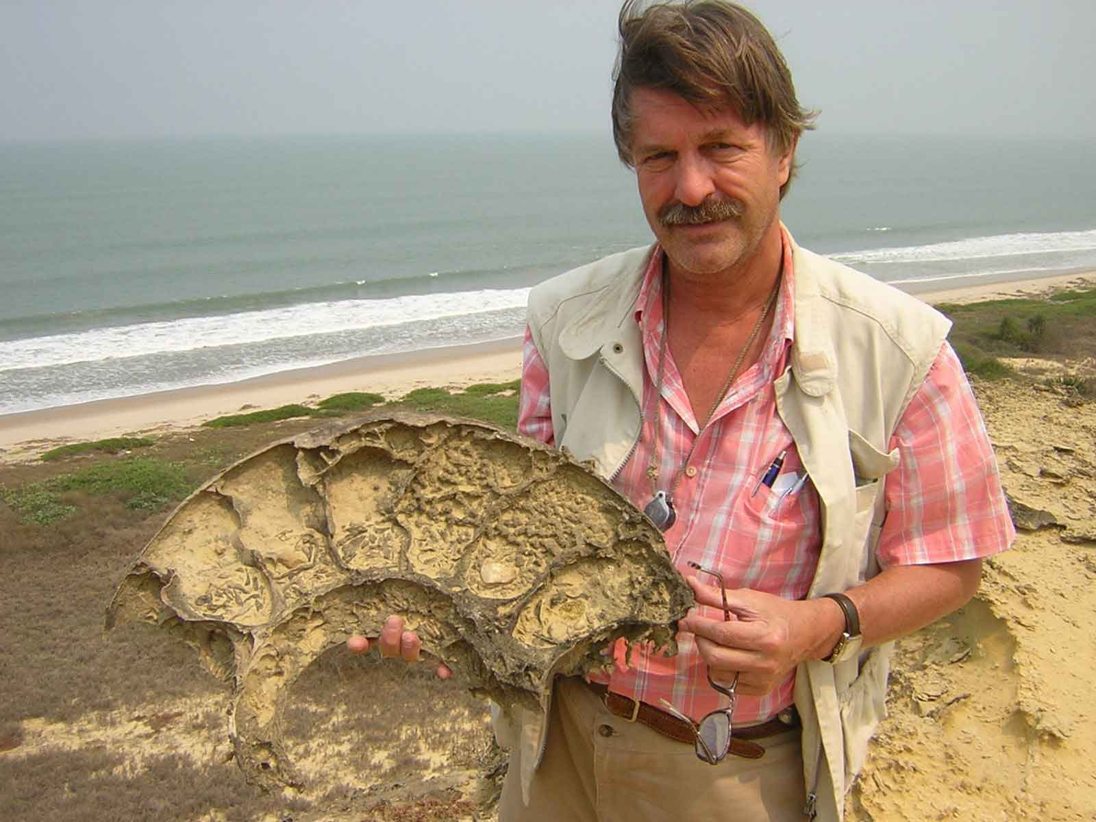An Angola Field Group member holds a Giant Cretaceous-age fossilized ammonite unearthed along Angolan coast
