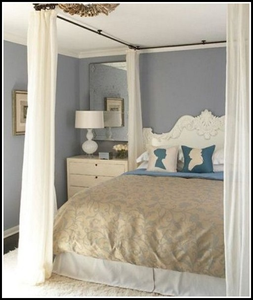 Curtain Rods Hang From The Ceiling To Simulate A Canopy Bed