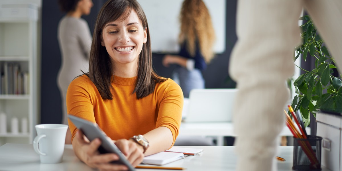 woman in orange sweater showing man tablet