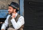 Jude Law está com um chapéu coco preto e usando um terno cinza, sentado numa cadeira nos bastidores do segundo filme.