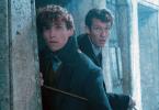 Foto de Newt e Teseu Scamander se escondendo atrás de um pilar de pedra. Eles olham para o alto.