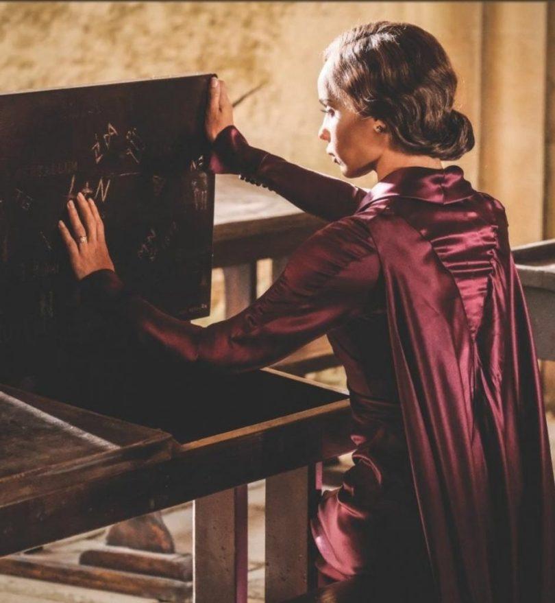 Leta adulta observa um rabisco numa banca de Hogwarts: L+N.