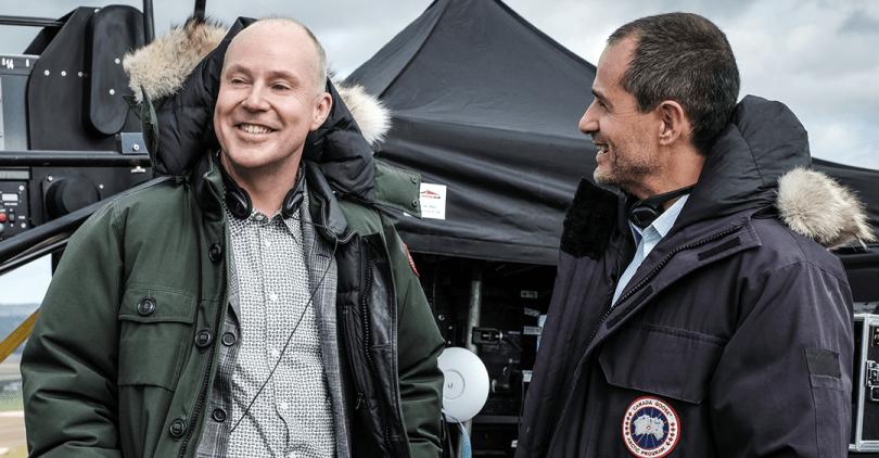 David Yates e David Heyman conversam em set de Animais Fantásticos: Os Crimes de Grindelwald. Heyman olha para Yates e Yates está olhando para frente. Os dois estão sorrindo e com roupas de frio pesadas. Por trás deles, vemos uma tenda preta com diversos equipamentos de filmagem.
