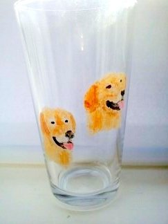 Two golden retriever glass paintings on a pint glass
