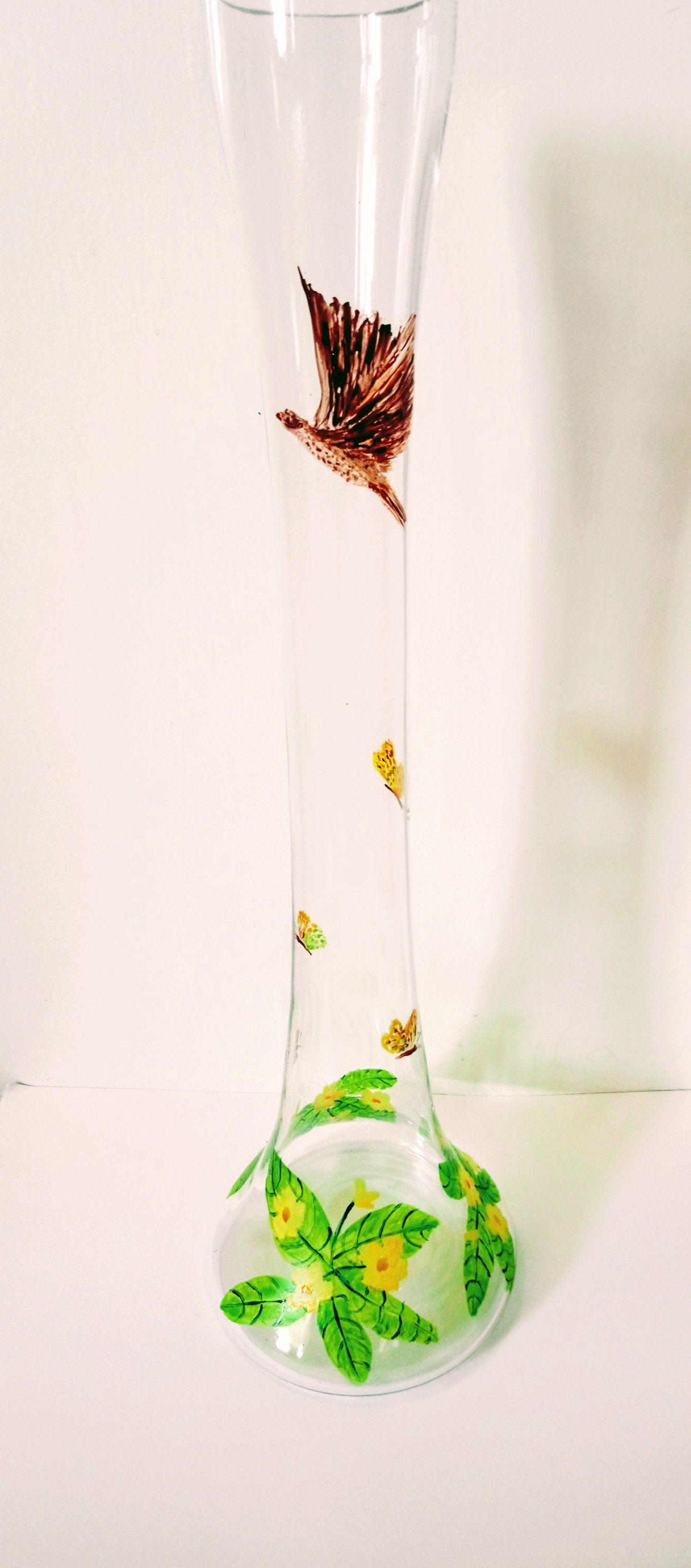 Lily vase with primroses and a bird
