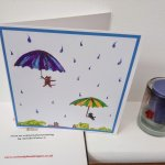 Funny card with a cat and dog in the sky with umbrellas and raindrops around them.