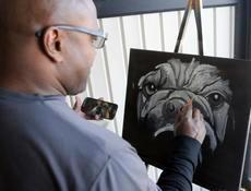 Local artist Tony Graves paints a black and white portrait of a dog Saturday at the Pup-Tacular Harvest Celebration.
